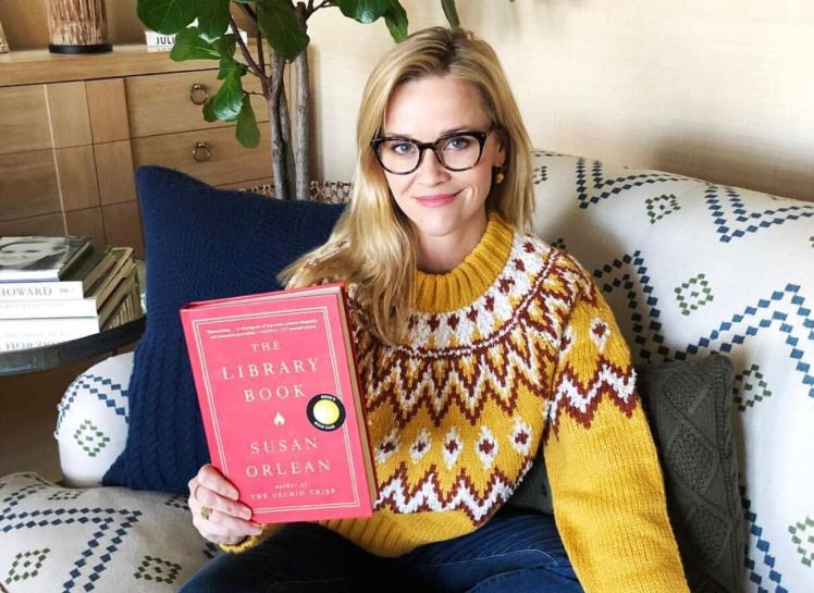 "Reese Witherspoon sitting on a patterned couch holding a copy of ""The Library Book"" by Susan Orlean."