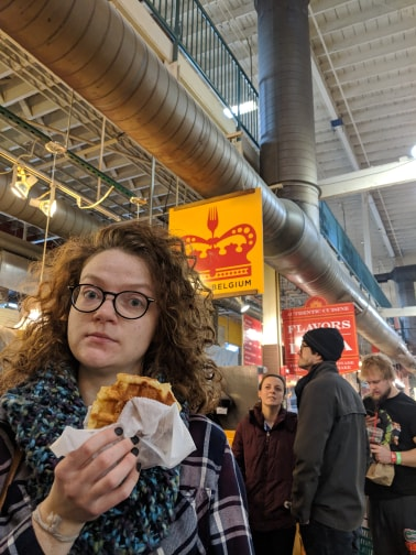 Image of Leann holding a good waffle in front of Taste of Belgium looking at the camera.