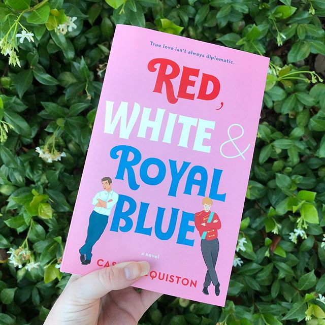 Image of the cover of Red, White, and Royal Blue, being held against a green shrubbery.